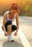 mulher jovem fitness amarrar cadarços na estrada