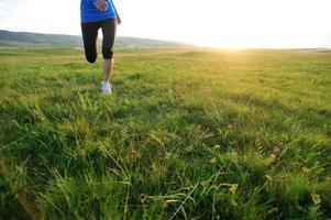 pernas de atleta corredor correndo no campo de grama ensolarada foto