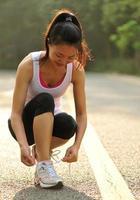 mulher jovem fitness amarrar cadarços na estrada foto