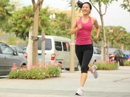 mulher asiática de esportes, movimentando-se no parque da cidade foto