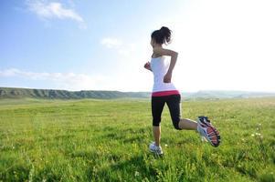 atleta corredor correndo no nascer / pôr do sol campo de grama foto