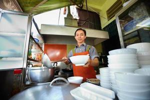 homem cozinhando e servindo sopa em tigelas no restaurante foto