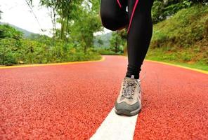 estilo de vida saudável fitness esportes pernas de mulher correndo na trilha do parque foto