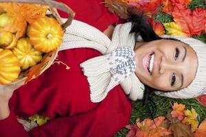 mulher sorridente com cesta de abóboras foto