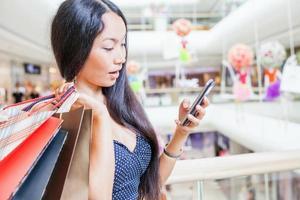 moda mulher asiática com saco usando telefone celular, shopping center foto