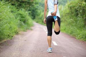 atleta corredor, esticar as pernas foto