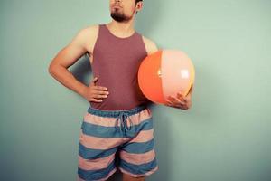 jovem, segurando uma bola de praia foto