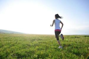 atleta corredor correndo nas pastagens foto