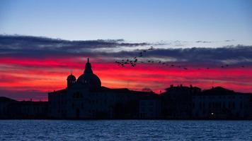 céu vermelho ao nascer do sol em Veneza perto do grande canal foto