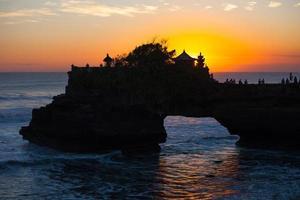 pôr do sol sobre o templo hindu pura tanah lot, bali, indonésia foto