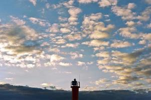 topo do farol em um fundo azul céu nublado foto