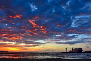 pôr do sol sobre o mar com farol foto