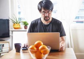 homem trabalhando no laptop, em casa foto