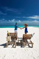 casal de azul em uma praia nas Maldivas