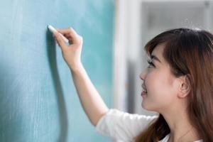 mulher bonita asiática, escrevendo no quadro-negro foto