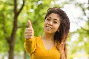 mulher bonita, gesticulando polegares acima no parque foto