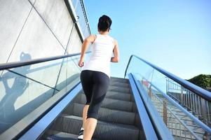 atleta corredor correndo nas escadas rolantes. foto