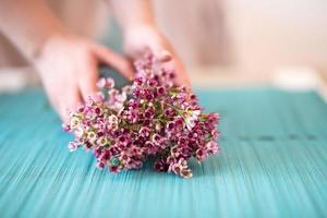 florista fazendo buquê de flores de cera foto