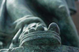 pé esverdeado esverdeado de uma estátua foto