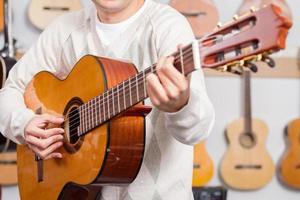homem tocando violão na loja de música foto