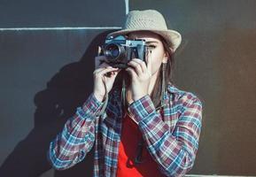 menina bonita hippie no chapéu fazendo foto com câmera retro