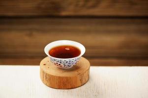 chá preto puerh em tigela branca no carrinho de madeira foto