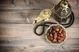 lâmpada do Ramadã, Rosário e datas em fundo de madeira foto