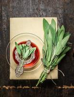 xícara de chá de ervas sálvia com filtro velho, livros