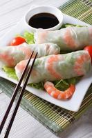 rolinho primavera com camarão e molho em um prato. vertical foto