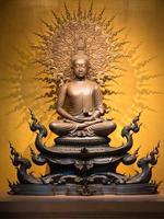 escultura dourada de Buda em posição de lótus, sentado foto