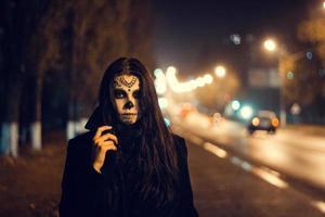 mulher bonita com maquiagem de caveira de açúcar de halloween na rua