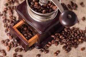 moedor de café antigo e grãos de café foto