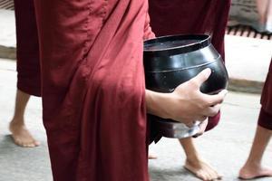 monge birmanês carregando tigela implorando foto