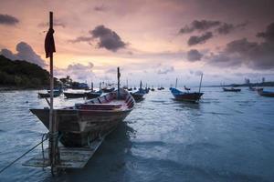 na hora por do sol com os barcos e o céu laranja foto