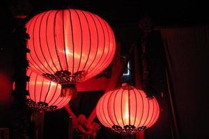 lanternas chinesas vermelhas e alaranjadas iluminadas no escuro foto