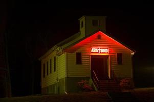 Jesus salva sinal em néon vermelho, porta da igreja à noite foto