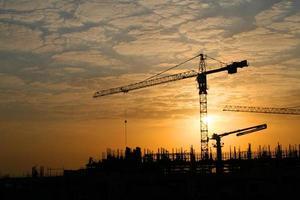 guindastes de construção em silhueta contra o sol da manhã foto