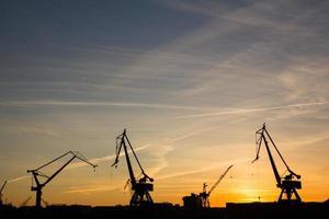 guindastes portuários ao pôr do sol foto