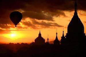 pagode silhueta no nascer do sol e balão em bagan, myanmar foto