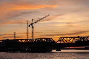 belo pôr do sol com postes de construção foto