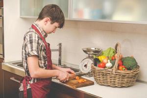 menino prepara legumes na cozinha - pessoas saudáveis vegetarianas