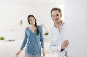 casal alegre, convidando as pessoas a entrar em casa foto