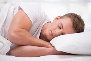 jovem dormindo debaixo de um cobertor foto