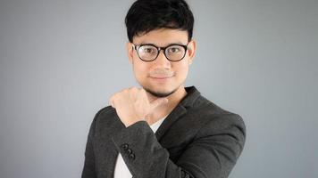empresário asiático de terno preto com fundo cinza. foto