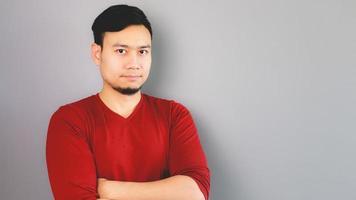 homem asiático de camiseta vermelha está cruzando os braços. foto