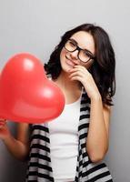 garota bonita e atraente, com um coração nas mãos. foto