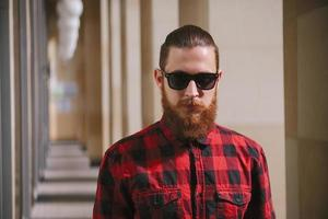 óculos de sol barbudo hipster na cidade foto