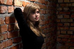 retrato de menina bonita em pé perto da parede de tijolo vermelho foto