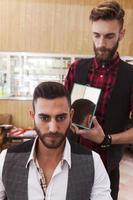 barbeiro hipster jovem mostra o corte de cabelo para um cliente
