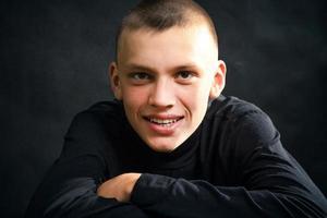 close-up do jovem com as roupas pretas, sorrindo foto
